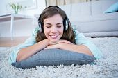 stock photo of muse  - Peaceful woman listening musing lying on the floor at home in the living room - JPG