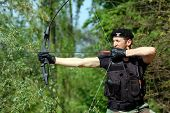 stock photo of bow arrow  - The soldier shoots with bow and arrow in the forest - JPG