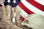 foto of veterans  - Old combat boots dog tags and helmet with American flag in the background closeup - JPG