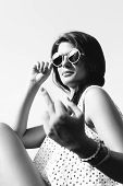 image of rude  - Fashion outdoor black and white portrait of young beautiful sensual woman in summer having fun sitting on the street in sunglasses in evening sunset Girl showing rude gesture - JPG