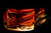 picture of refraction  - in the base of a bottle of cognac fiery red bright lights are glowing wavelike  - JPG
