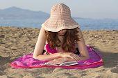 stock photo of sunbather  - Woman enjoying her book while sunbathing on the beach - JPG