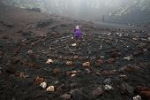 stock photo of supernatural  - Child standing in center of a spiritual spiral of igneous rock in Etna volcano crater - JPG