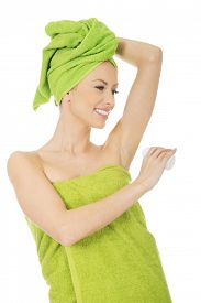 image of deo  - Young woman wrapped in towel using deodorant - JPG