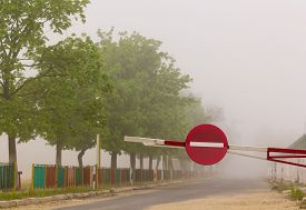 picture of no entry  - Barrier with no entry traffic sign on road in fog - JPG