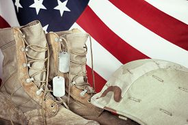 pic of veterans  - Old combat boots dog tags and helmet with American flag in the background closeup - JPG