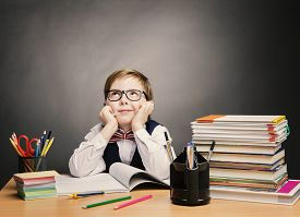 stock photo of classroom  - School Child Boy in Glasses Think in Classroom Kid Primary Students Reading Book Excellent Pupil Learn Lesson and Dream Education Concept - JPG