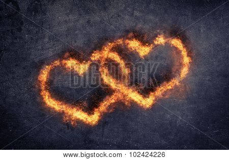 Couple of decorative overlapping flaming hearts with fiery orange flames for valentines day or a wed