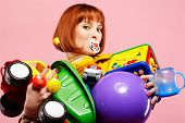 picture of red hair  - portrait of redhead woman posing with various toys on pink - JPG