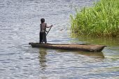 Young Boy Paddling A Dugout In Lake Malawi
