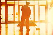 Janitor mopping in an office building poster