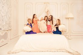 stock photo of pillow-fight  - cheerful girls staged a pillow fight on the bed - JPG