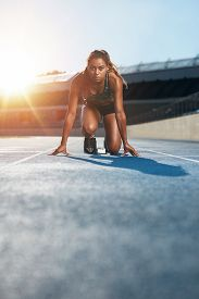 foto of sprinters  - Vertical shot of young female sprinter taking ready to start position facing the camera - JPG