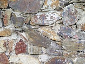 stock photo of old stone fence  - wall texture of old stones worn colors - JPG