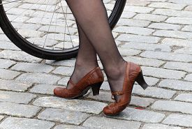 stock photo of panty-hose  - Closeup of a womans legs in old fashioned leather shoes and panty hose with cycle wheel in the background - JPG