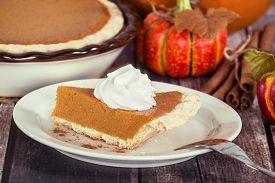 stock photo of pumpkin pie  - Slice of a pumpkin pie on wooden table - JPG