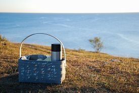 picture of thermos  - Basket with coffee thermos on ground by the coast - JPG