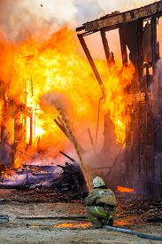picture of firemen  - Fireman extinguishes a burning old wooden residential house - JPG