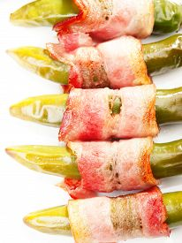 stock photo of jalapeno  - Grilled jalapenos wrapped in bacon isolated on white - JPG