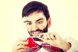 stock photo of scalpel  - Determined man wearing suspenders cutting heart model with scalpel - JPG