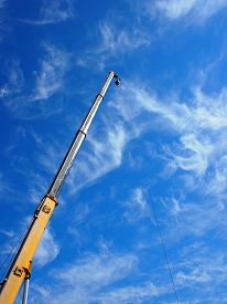 foto of boom-truck  - The boom of the crane on a diagonal against a blue sky with white cirrus clouds - JPG