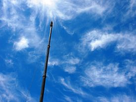 stock photo of boom-truck  - Upward view on the boom of a crane against the blue sky with white cirrus clouds - JPG