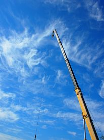 picture of boom-truck  - The boom of the crane on a diagonal against a blue sky with white cirrus clouds - JPG
