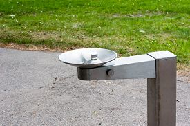 picture of fountain grass  - Empty silver metal water drinking fountain near park path and grass - JPG
