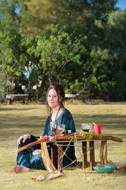 stock photo of sabbatical  - Beautiful polytheist woman in blue sitting outdoors - JPG