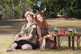 stock photo of sabbatical  - Two smiling pagan women at outdoor altar with pentagram - JPG
