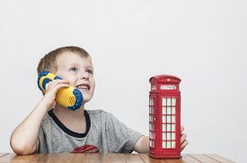 foto of phone-booth  - Little cheerful boy talking on the phone and vintage british red telephone booth - JPG