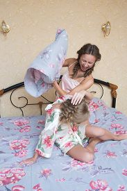 pic of pillow-fight  - Two beautiful young woman fighting with pillows in bed - JPG