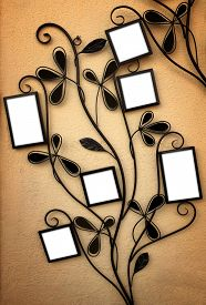stock photo of six-petaled  - Curly iron picture holder with 6 empty frames leaning on a yellow wall - JPG