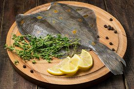 image of flounder  - Flounder with pepper thyme and lemon on a round cutting board and wooden table - JPG