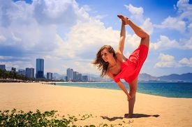 picture of short legs  - blond slim girl in short red frock stands in gymnastic position leg scale on sand beach against azure sea and city - JPG