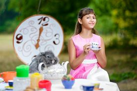 picture of alice wonderland  - Girl sits at table and holding a cup of tea - JPG