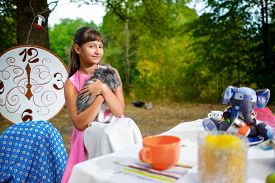 pic of alice wonderland  - Girl sits at table and holding a rabbit - JPG