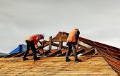 stock photo of purlin  - Pair of demolition workers wrecking roof of commercial building - JPG