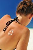 Sunscreen lotion over tan woman skin made as sun shape