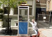 Girl On Cell Phone Near Phone Booth