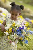 Young African American girl holding bouquet of flowers outdoors