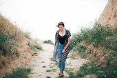 Stylish Hipster Girl Walking  Between Sandy Cliffs With Grass At Sunset. Happy Young Boho Woman Expl poster