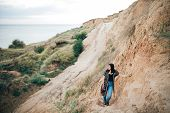 Stylish Hipster Girl Relaxing On Sandy Cliff And Holding Photo Camera.  Happy Young Boho Woman Explo poster
