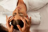 stock photo of pressure point  - Young woman enjoying head massage or cosmetic treatment in Spa - JPG