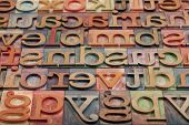 abstract of vintage wooden letterpress printing blocks stained by color inks, placed in a random order, selective focus