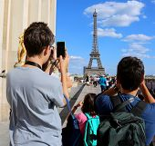 Young Tourists Take Pictures Of Eiffel Tower In Paris France From Trocadero Quartier poster