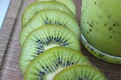 Kiwi Smoothies In A Glass Next To Fresh Kiwi Slices On A Blue Wooden Table. Fruit Drink.copy Space poster