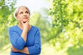 old people and decision making concept - portrait of senior woman in blue sweater thinking over grey poster