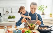 Healthy food at home. Happy family in the kitchen. Father and child daughter are preparing proper me poster