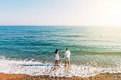 Happy Couple On The Beach With Their Backs To The Camera. Honeymoon Trip. The Couple Are Traveling.  poster